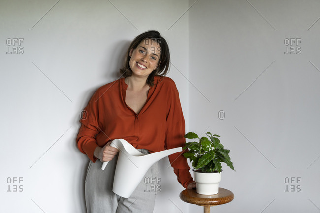 Portrait of smiling entrepreneur watering plants at home