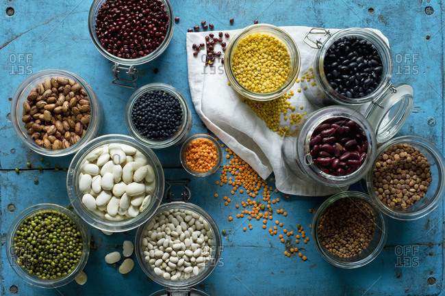 Various beans and lentils in jars on blue rustic wooden surface