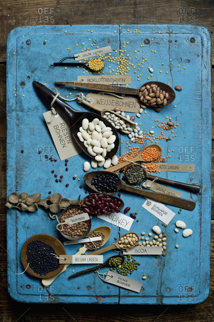 Various beans and lentils on blue rustic wooden surface