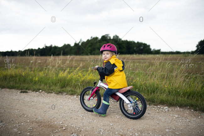 Toddler girl with pink cycling helmet on balance bicycle
