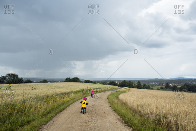 Girls with bicycle and balance bicycle on dirt track- rain clouds