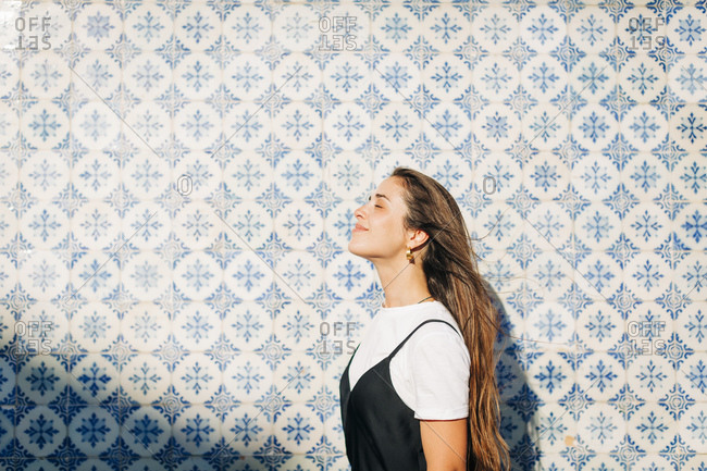 Smiling beautiful woman with eyes closed standing by tiled wall on sunny day