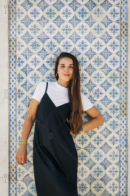 Smiling beautiful woman with long hair standing against tiled wall in city