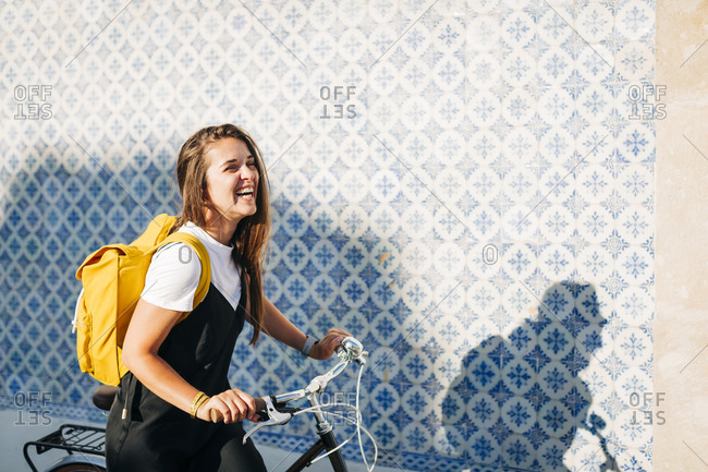 Cheerful woman with backpack riding bicycle by tiled wall in city on sunny day