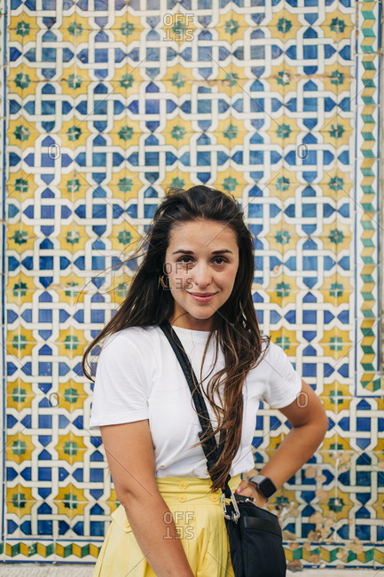 Smiling mid adult woman with long hair standing against tiled wall in city