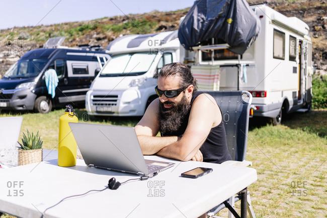 Man sitting next to camper using laptop on table
