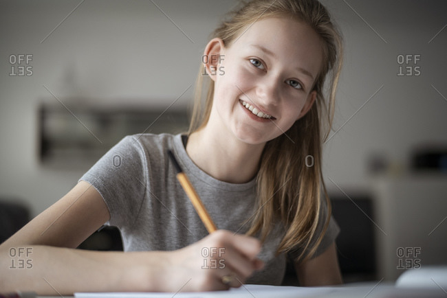 Smiling girl learning at home- writing in exercise book