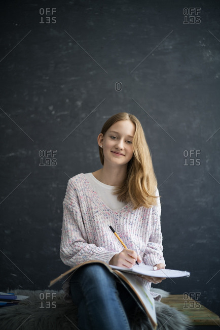 Girl learning at home- writing in exercise book