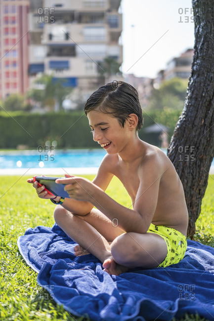 Shirtless boy playing video game over digital tablet while sitting on towel in yard