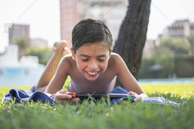 Shirtless smiling boy playing video game over digital tablet while lying on towel in yard