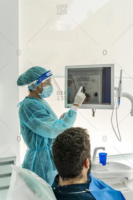 Female nurse talking to patient in dentist's clinic