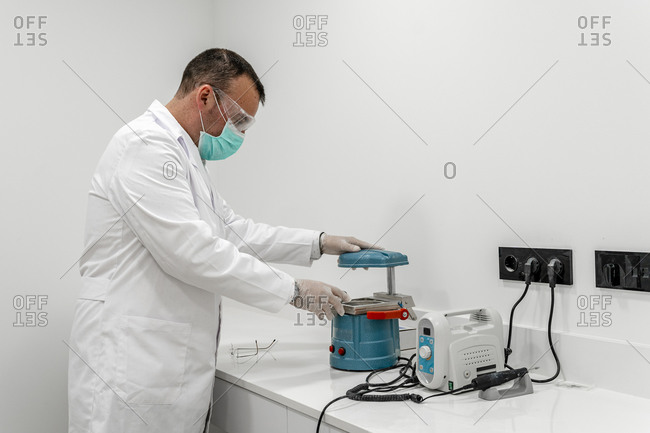Male dentist with research equipment at clinic