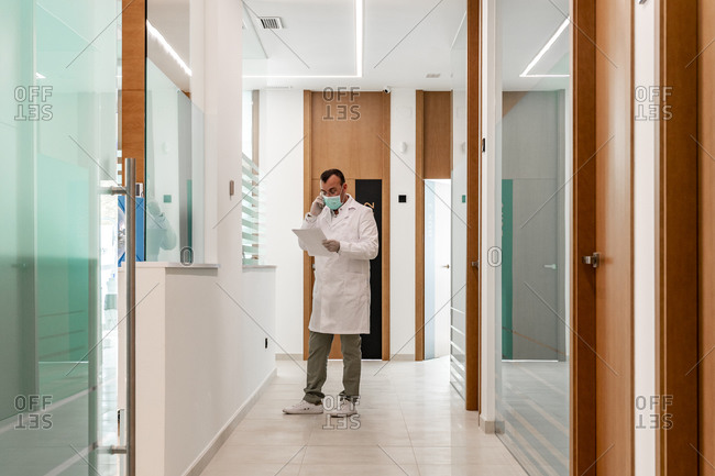 Dentist reading file while talking on phone in corridor at hospital