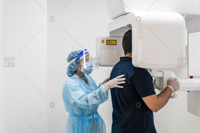 Female nurse helping male patient in scanning at hospital