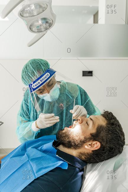 Female nurse examining patient in dentist's clinic
