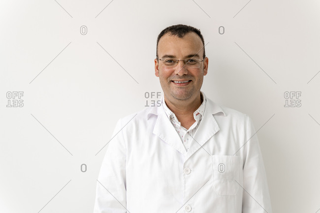 Smiling male doctor against wall in dentist's clinic