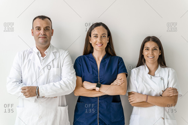 Smiling doctors with arms crossed against wall in dentist's clinic