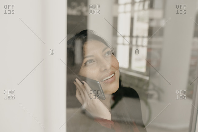 Portrait of smiling woman using smartphone behind window pane