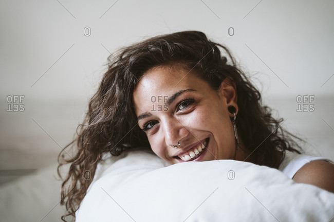 Close-up of cheerful young woman holding pillow against wall at home