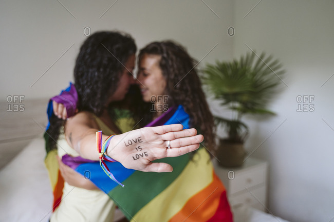 Young woman showing text of hand while embracing girlfriend at home