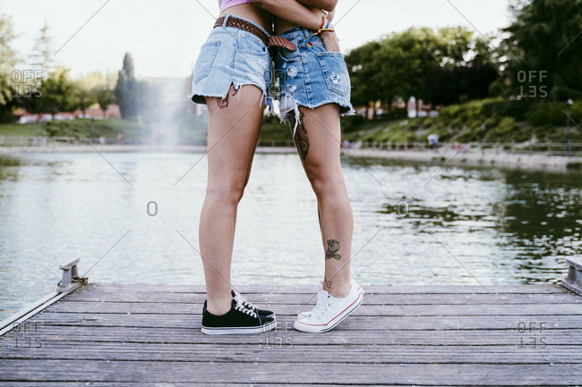 Lesbian couple wearing shorts standing on pier against lake