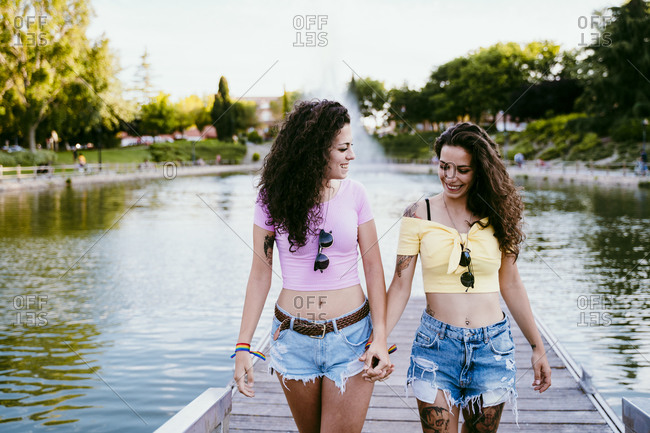 Lesbian couple holding hands while walking on pier against lake