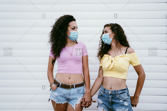 Lesbian couple wearing masks holding hands while standing against wall in city
