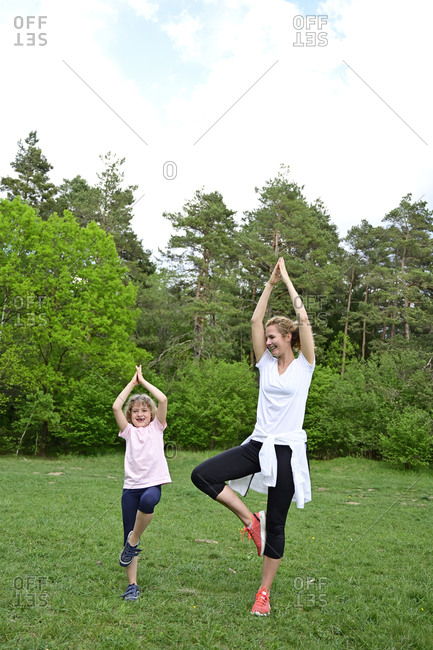 Mother with daughter practicing tree pose on grassy land in forest