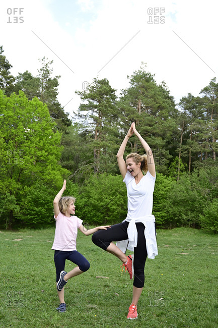 Happy mother and daughter practicing tree pose on grassy land in forest