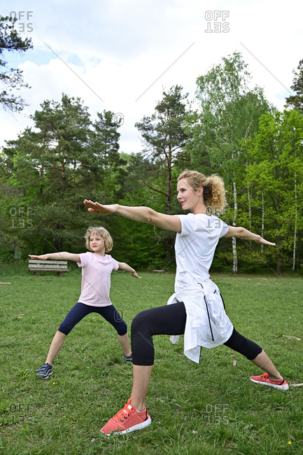 Mother with daughter practicing warrior 2 pose on grassy land in forest