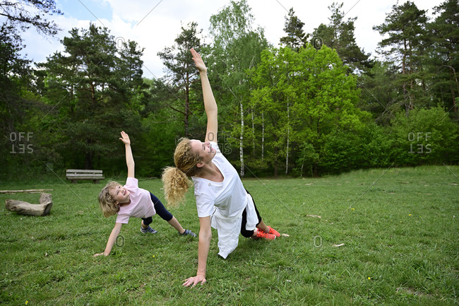 Mother and daughter practicing side plank pose on grassy land in forest