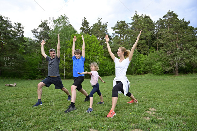 Family practicing warrior poses on grassy land in forest