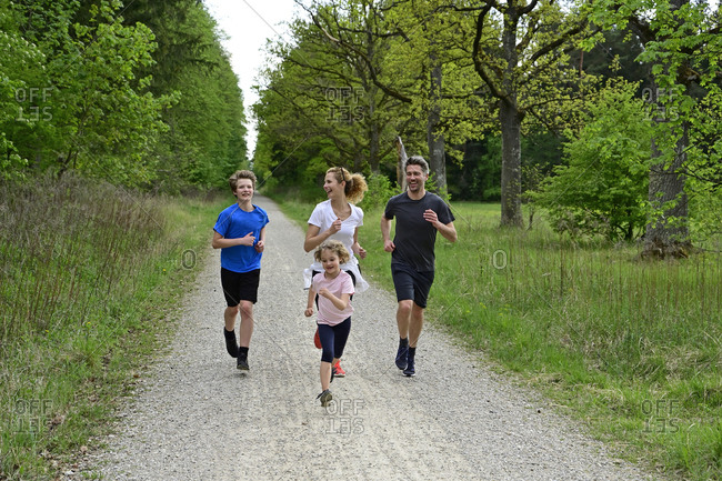 Cheerful family running on dirt road amidst trees and plants in forest