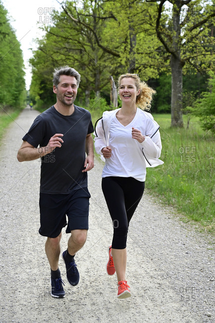 Happy couple running on dirt road against trees in forest