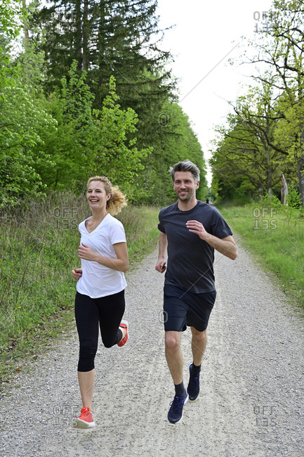 Smiling couple running on dirt road against trees and plants in forest