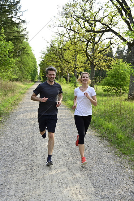 Happy couple jogging on dirt road against trees and plants in forest