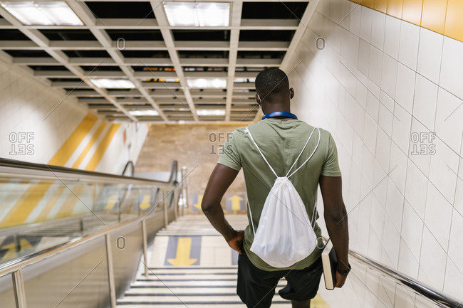 Young man with backpack moving down on steps in subway station