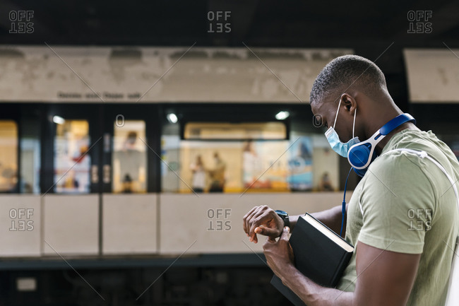 Young man wearing mask checking time while standing at subway station