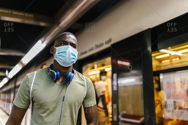 Young man wearing mask looking away while standing at subway station