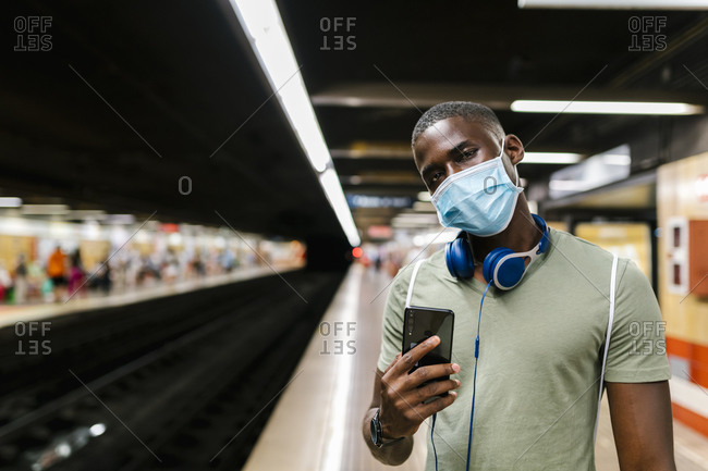 Young man wearing mask using smart phone while standing in subway station