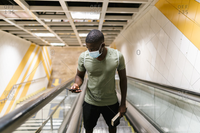 Young man wearing mask using smart phone while standing on escalator at subway station