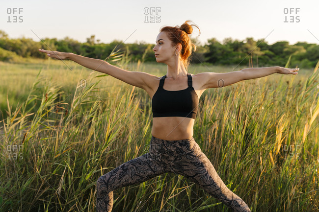 Woman practicing warrior two yoga pose on grassy field