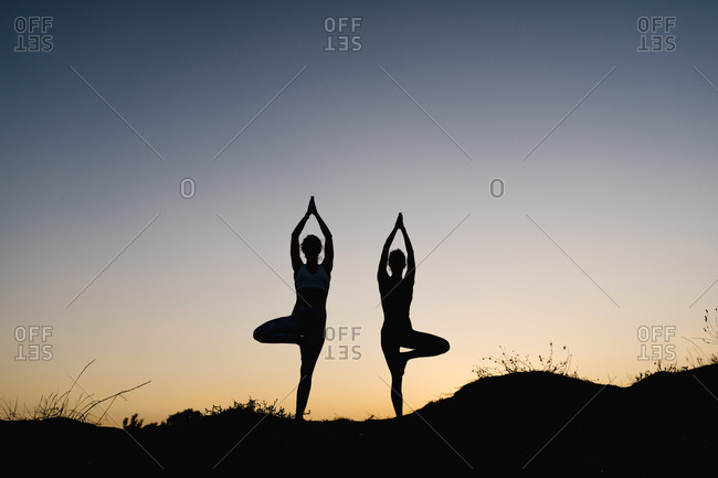 Women practicing practicing tree pose outdoors against clear sky