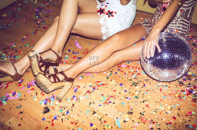 Female friends sitting on floor covered with confetti in party