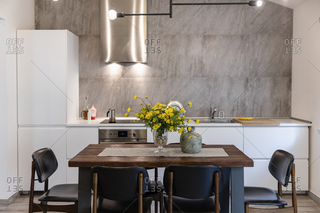 Dining table with chairs arranged in modern kitchen at home