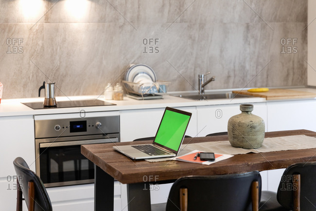 Laptop and smart phone on dining table in modern kitchen at home