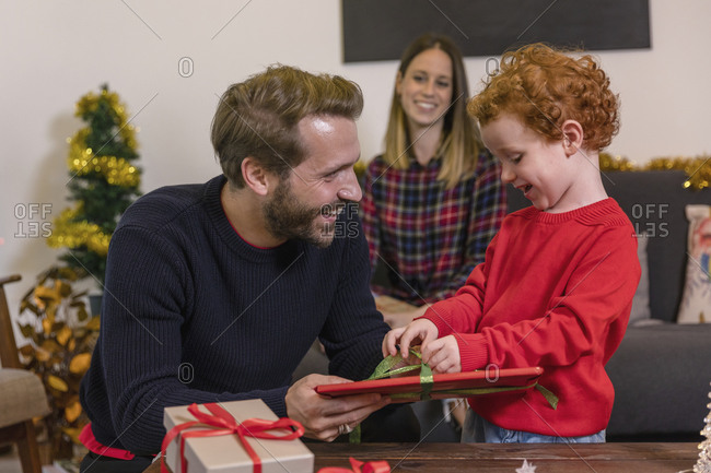 Smiling woman looking at father giving Christmas present to son in living room