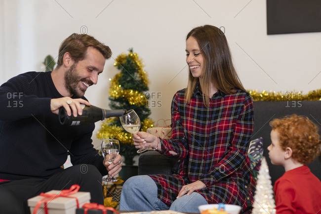 Boy looking at father pouring champagne to mother while sitting on sofa in living room during Christmas