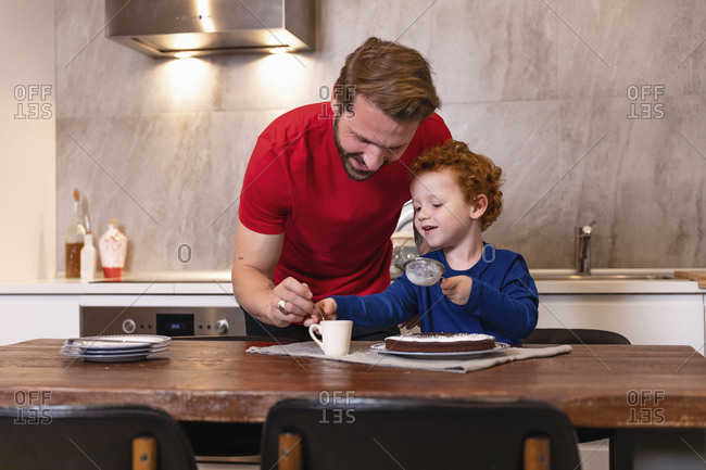 Happy father and son decorating chocolate cake on dining table in kitchen