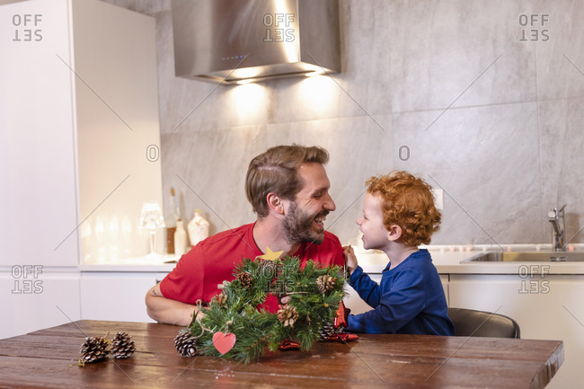 Cheerful father and son looking at each other while decorating Christmas wreath on dining table